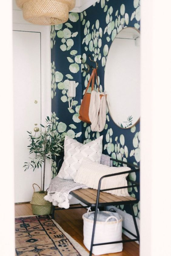 a refined entryway with realistic botanical wallpaper, a lovely bench, baskets and a potted olive plus a woven pendant lamp
