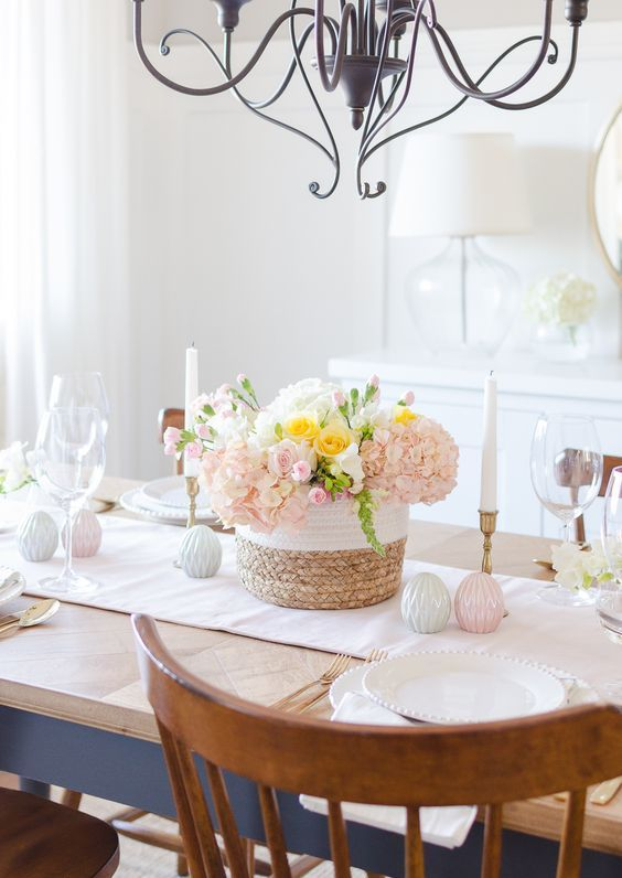 a refined pastel Easter tablescape with pastel blooms, pastel porcelain eggs, elegant candles and porcelain