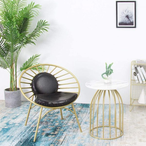 a refined space with a metal frame papasan chair, a refined table with a marble top, a boho rug and a potted plant