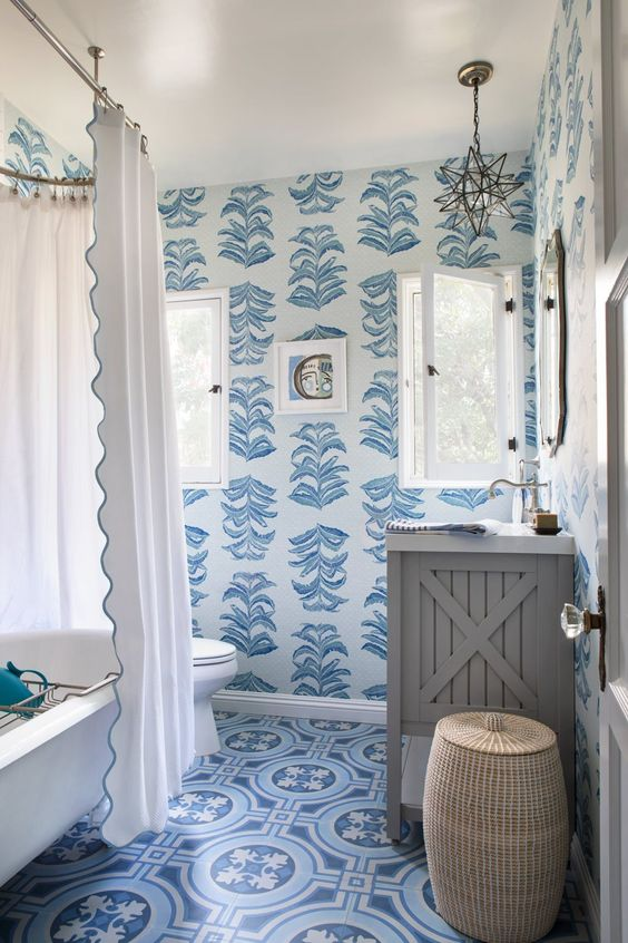 a refined vintage bathroom with blue botanical wallpaper, blue printed tiles and a refined star-shaped lamp