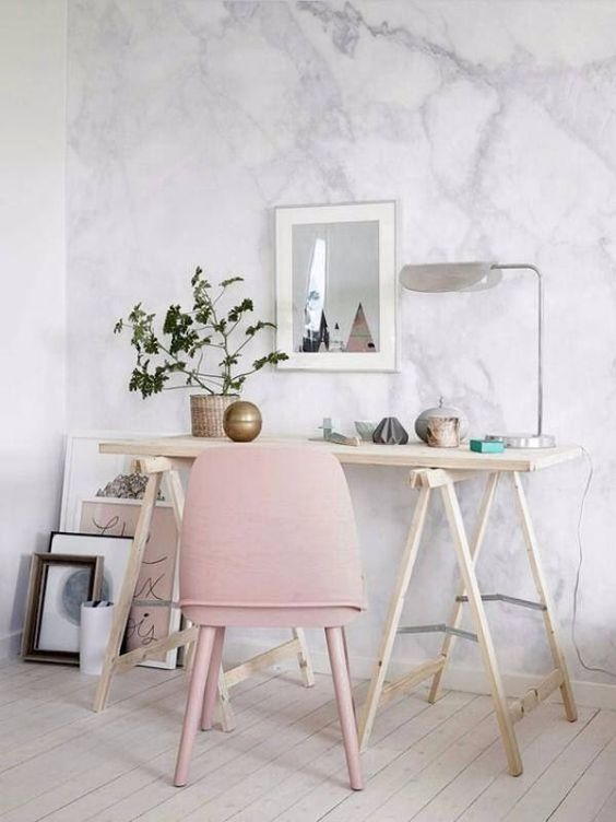 a romantic feminine home office with a simple trestle desk, a pink chair, potted greenery and vases and lamps