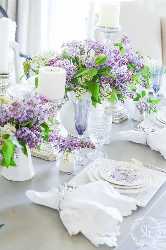 a romantic spring tablescape with lots of lilac, pillar candles, printed and white porcelain and white napkins
