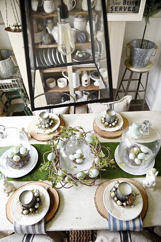a rustic Easter table setting with wood slices, striped napkins, tin can candles, vine wreaths with eggs