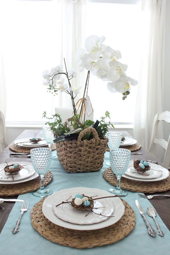 a rustic Easter tablescape with a blue runner, woven placemats, a basket with greenery and white orchids, mini nests with eggs