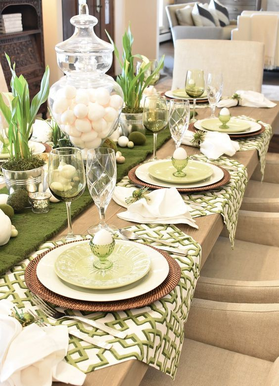 a rustic green and white Easter tablescape with printed napkins, woven placemats, moss, eggs, bunnies and greenery in tin cans