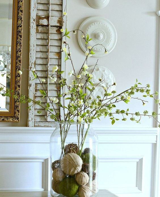 a rustic spring centerpiece of a jar with vine, moss and burlap balls and blooming branches looks creative and non-typical