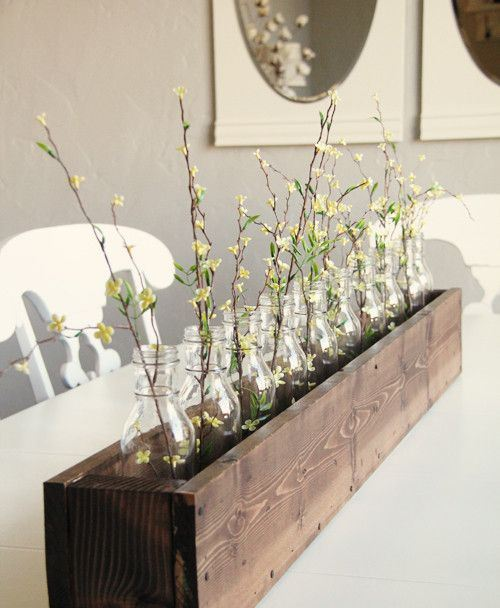 a rustic spring centerpiece of a wooden box, a row of bottles and yellow blooms is a stylish idea for spring