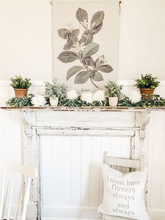 a rustic spring mantel with a greenery garland, potted greenery, some white blooms, candles and a plant and bloom print