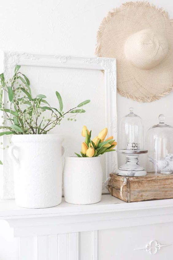 a rustic spring mantel with potted branches and tulips, a straw hat, a vintage frame, cloches with figurines