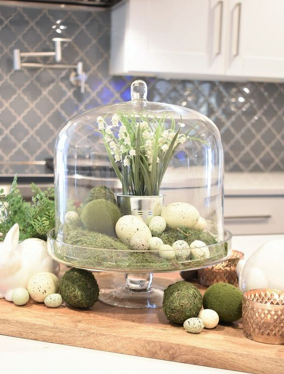 a rustic spring or Easter centerpiece of a cloche with moss, faux eggs, moss balls and a tin can with lily of the valley