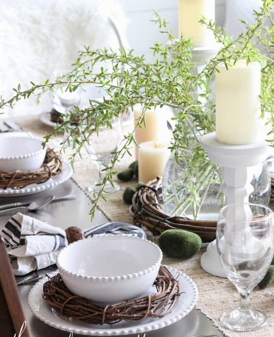 a rustic spring or Easter tablescape with greenery, candles, vine wreaths, wooden napkin rings and moss eggs