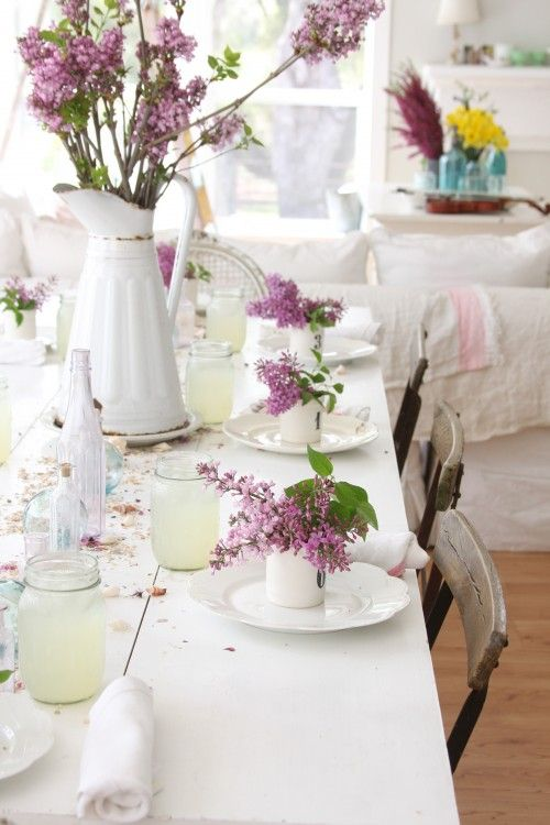 a rustic spring table setting with an uncovered table, white porcelain, lilac everywhere and fresh lemonade