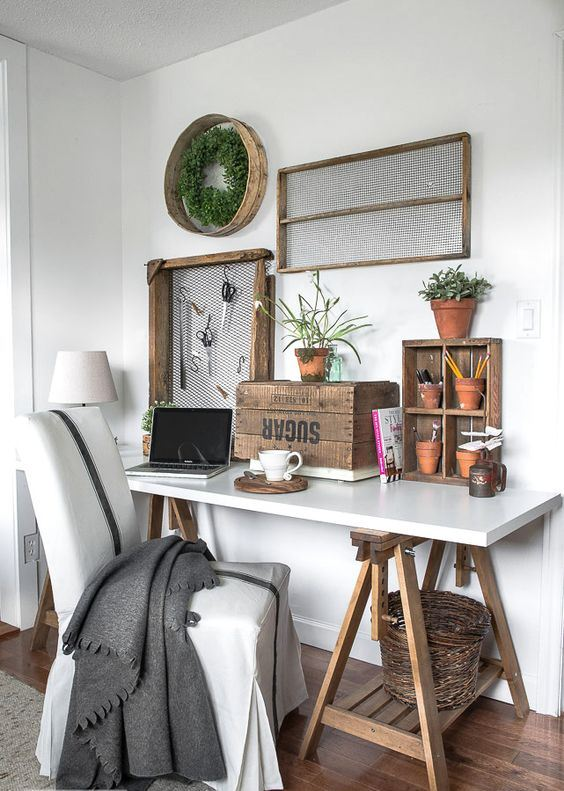 a rustic working space with a trestle desk and baskets, a box, crates and wire, with a wreath with greenery and a comfy chair