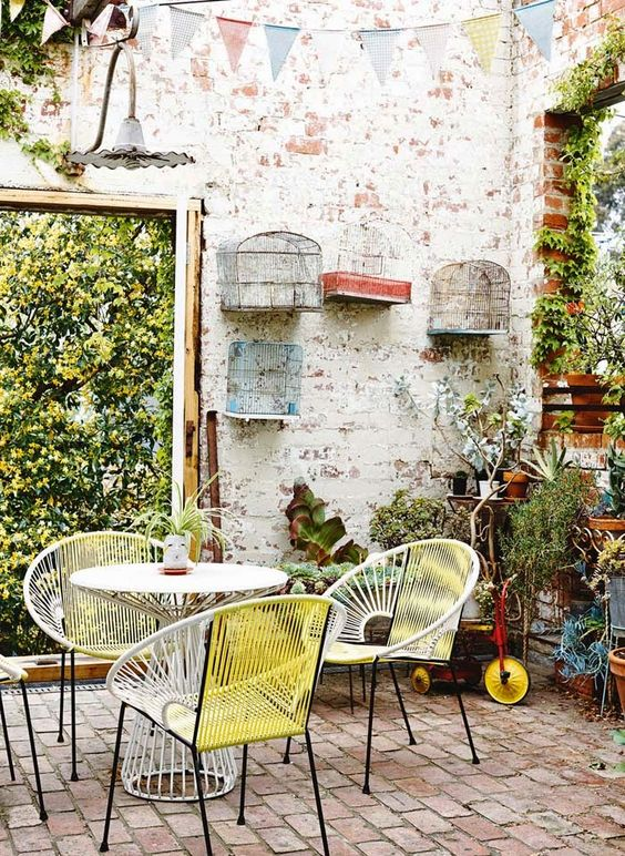 a shabby chic spring terrace with brick walls, greenery and plants covering the wall and corner, pretty mid-century modern furniture