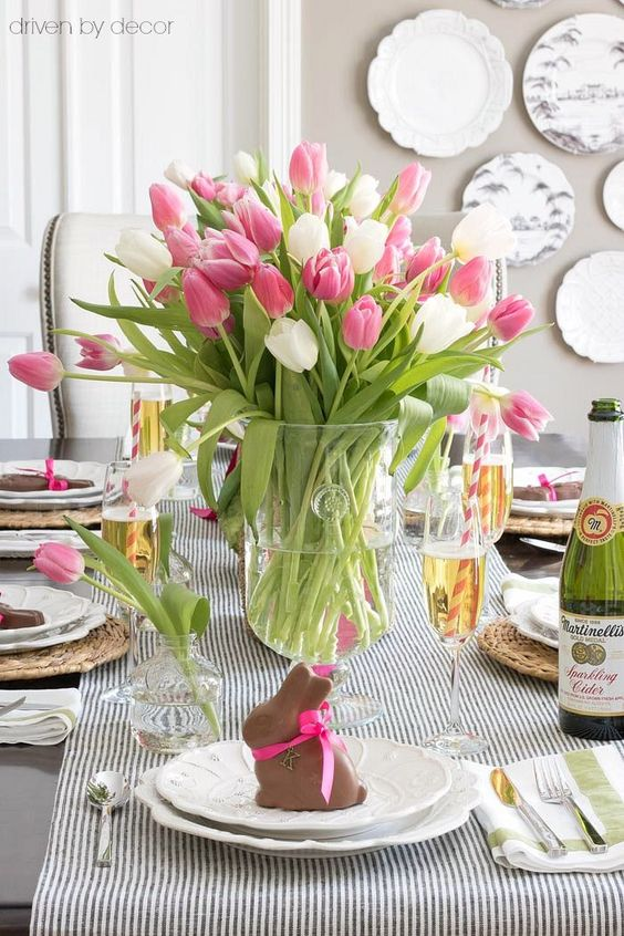 a simple Easter tablescape with a striped runner, woven placemats, vintage porcelain and chocolate bunnies for each palce setting