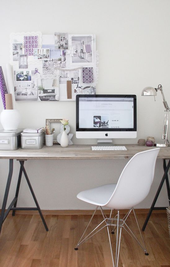 a simple Scandinavian home office with a modern trestle desk, a white chair, a gallery wall and a table lamp plus metal boxes