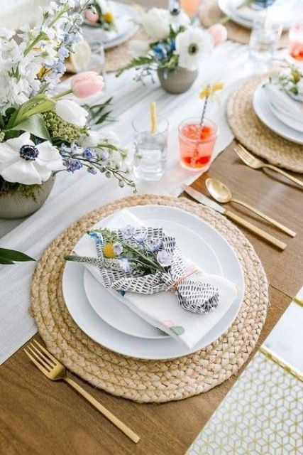 a simple and bright spring tablescape with a white runner and printed napkins, woven placemats, gold cutlery, neutral and pastel florals