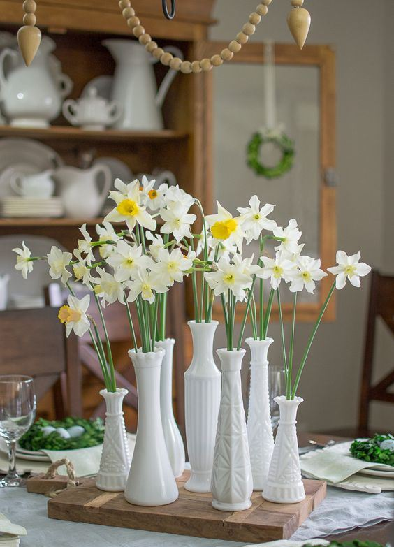 a simple and natural spring cluster centerpiece of textural vases with white daffodils is a beautiful decoration to rock