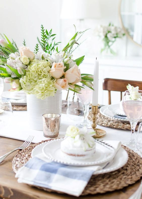 a simple and pretty spring tablescape with woven placemats, plaid napkins, white porcelain, pastel and neutral floral centerpiece