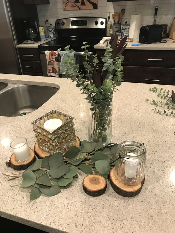 a simple eucalyptus centerpiece in a vase, with candles on wood slices is a lovely and simple idea for many occasions
