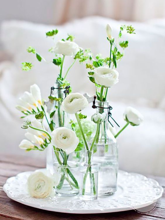 a simple spring cluster centerpiece of glasses and vases, with white blooms and greenery is a lovely idea for any season