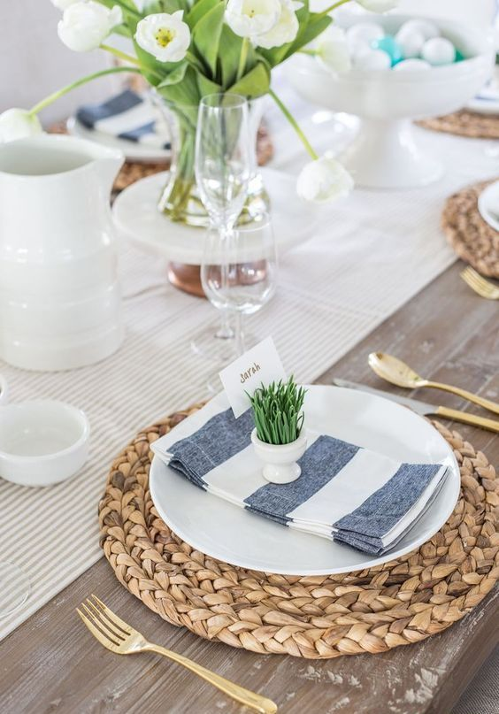 a simple spring tablescape with a striped runner, woven placemats, striped napkins, white tulips and egg holders with grass