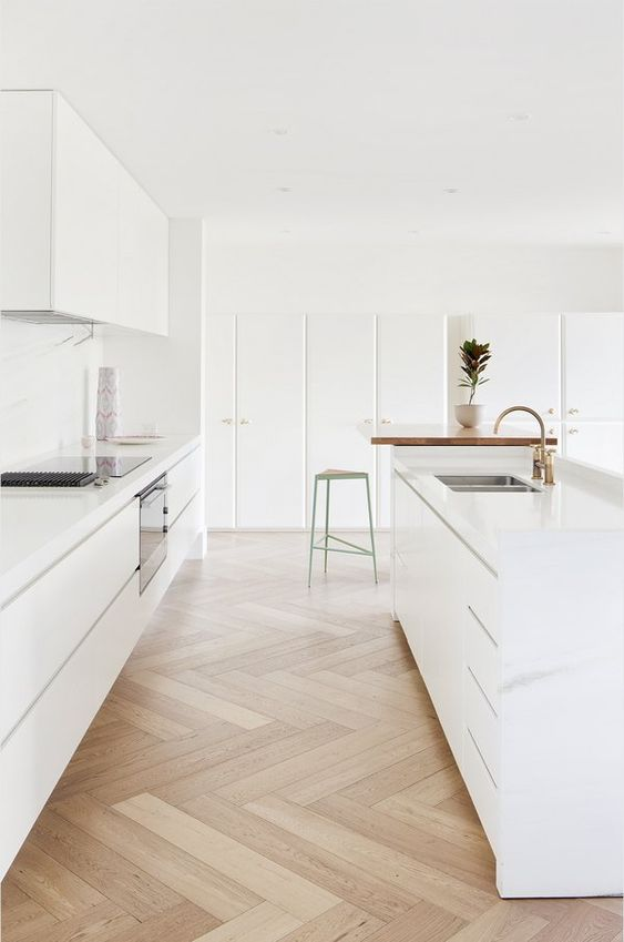 a sleek minimalist kitchen with a large kitchen island, a white marble backsplash and gold touches here and there