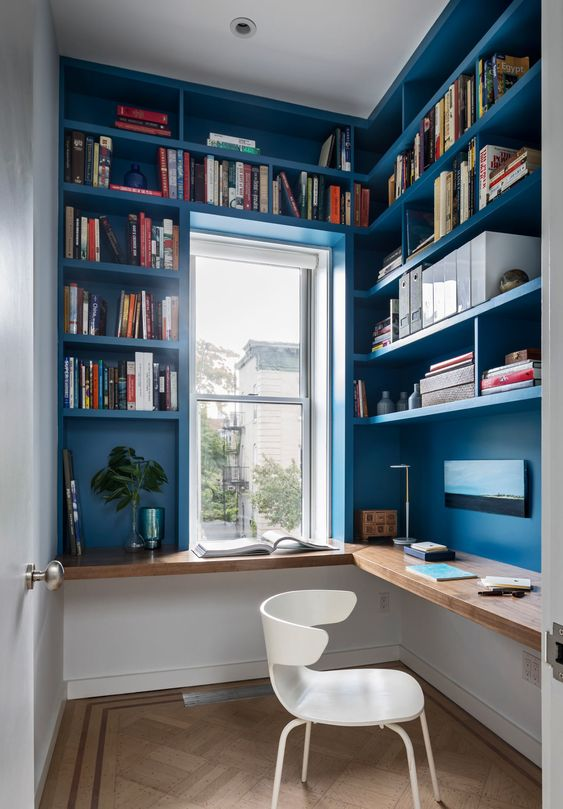 a small and bright home office with bold blue walls and built-in shelves, a floating corner desk and a window is a cool space to be in