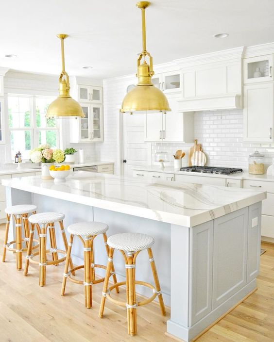 a small and cozy coastal kitchen with white cabients, a white subway tile backsplash, a grey kitchen island with a marble counter and rattan stools