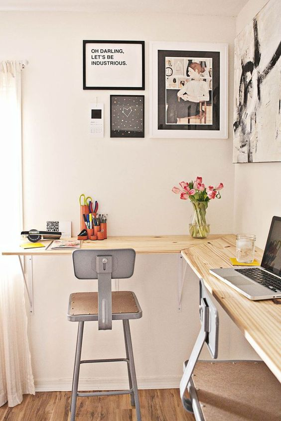 a small and cozy shared home office with a floating wooden corner desk, metal chairs, a gallery wall and blooms