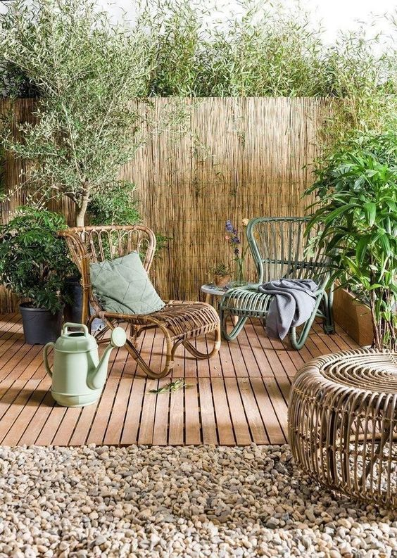 a small and cozy terrace with rattan loungers, potted plants and trees, a rattan table and a watering can