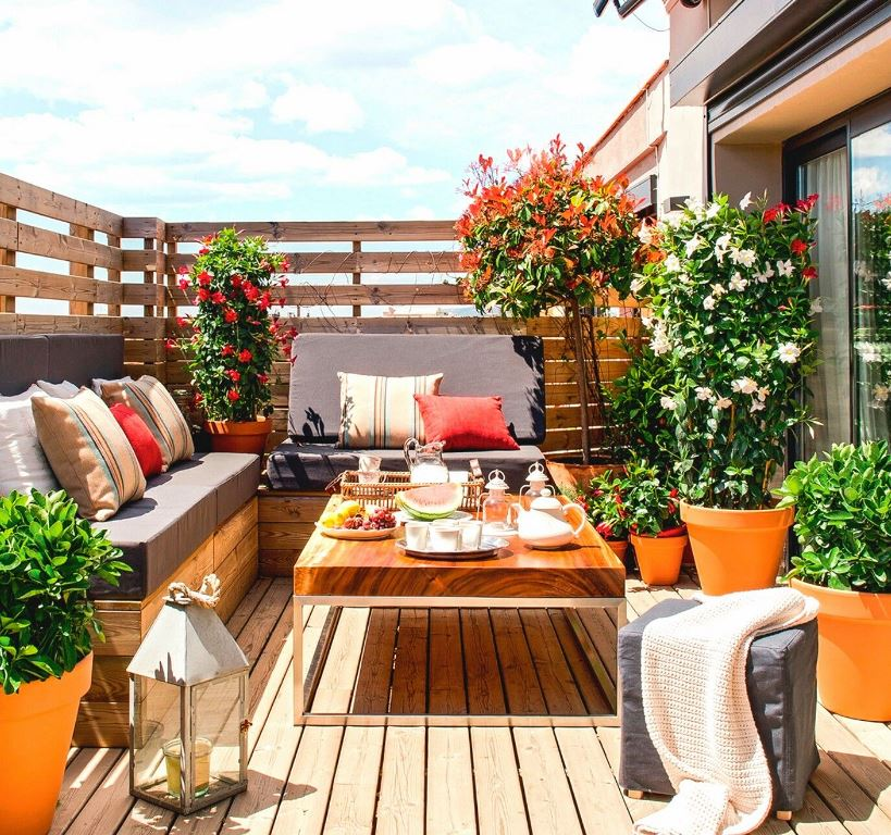 a small colorful terrace with a built in corner seat, a table, potted greenery and blooms and a candle lantern