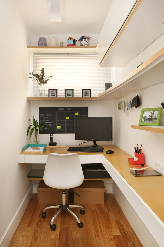 a small home office space with a closed storage unit and an open shelf, a floating corner desk, a white chair and some plants and art