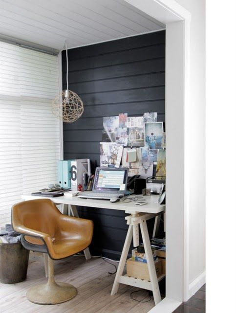 a small home office with a black statement wall, a white trestle desk, a gallery wall and a pendant lamp is cozy and cool