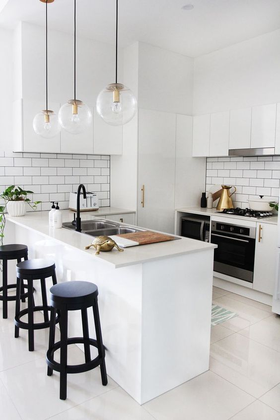 a small white kitchen with a subway tile backsplash, black fixtures and black stools and pendant bubble lamps