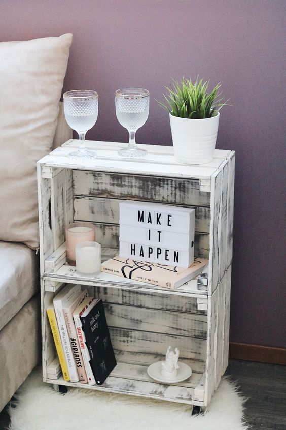 a small whitewashed nightstand of two crates, with books and candles, with potted plants and glasses is great for a bedroom