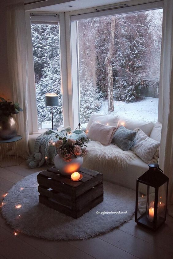 a sofa built into the space by the ay window, with lots of blankets and pillows, a crate table with blooms and candles