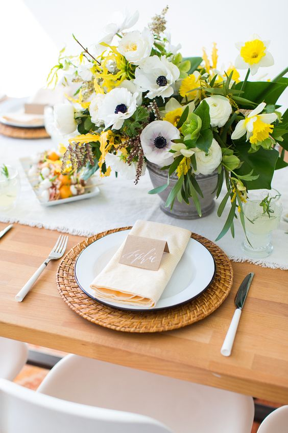 a spring brunch tablescape with woven chargers, white porcelain, white cutlery and a yellow and white floral centerpiece