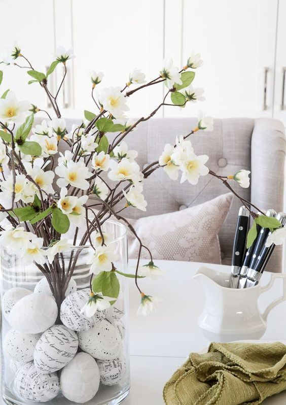 a spring centerpiece of a vase, with handwritten eggs, blooming branches is a classic centerpiece idea for spring