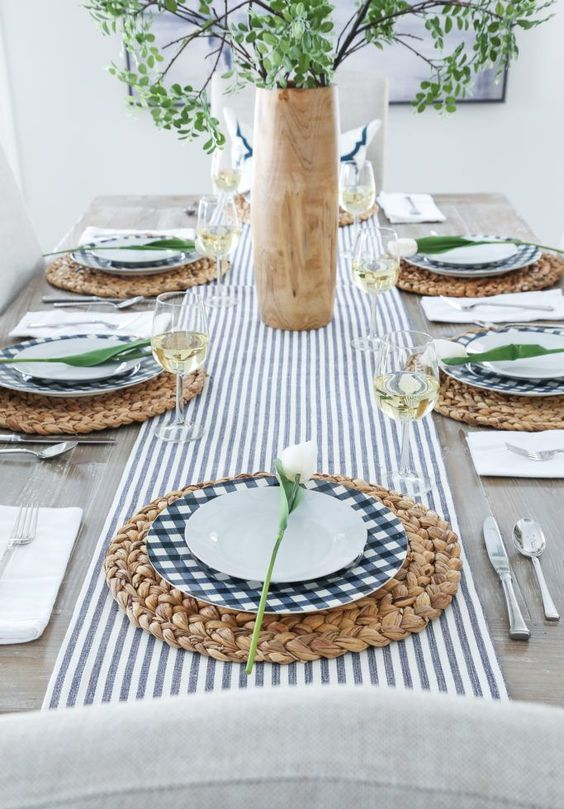 a spring table setting with a striped runner, woven placemats and plaid plates, greenery and white blooms
