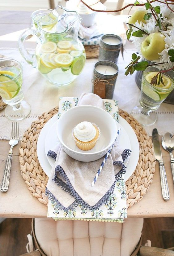 a spring tablescape with woven chargers, printed napkins, white porcelain, white blooms and fresh druits plus candles