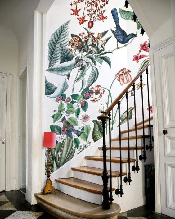 a staircase space highlighted with bright floral wallpaper and a whimsical lamp looks just jaw dropping and wow