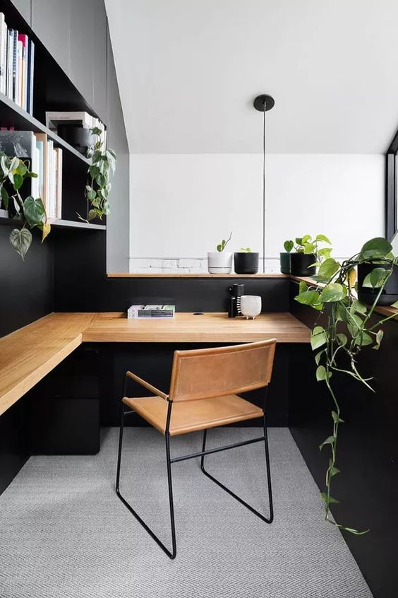 a stylish Scandinavian home office in black, with a light stained wooden corner desk, a leather chair and potted greenery