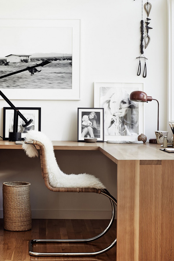 a stylish Scandinavian home office with a corner desk, black and white artworks, wooden beads and a metal lamp and a woven chair