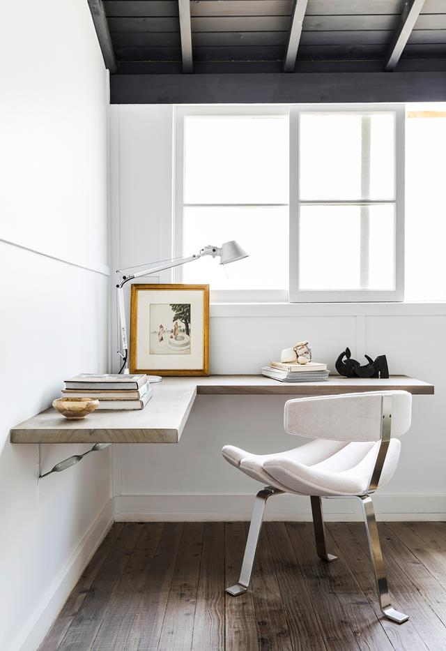 a stylish Scandinavian home office with a floating corner desk, a quirky chair with three legs, some books and artworks
