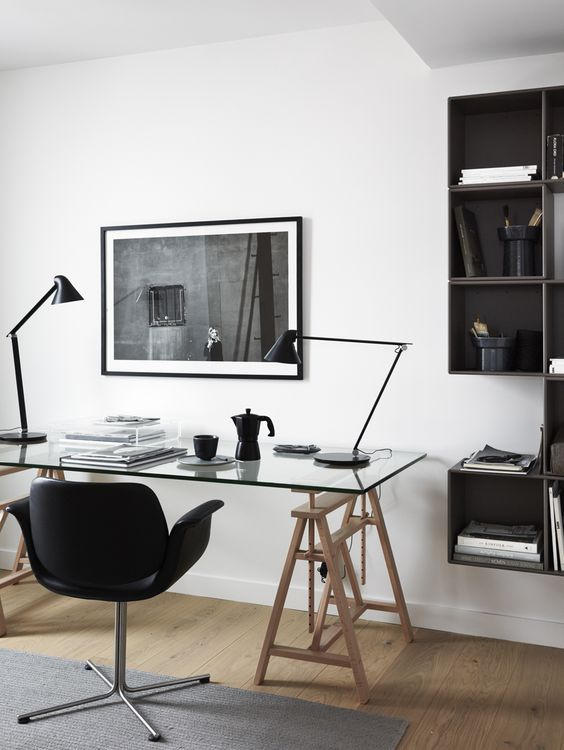 a stylish contemporary home office with a glass and wood trestle desk, a black chair, table lamps and an open storage unit
