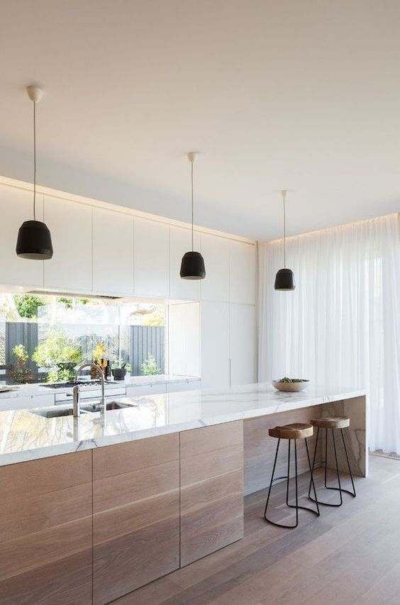 a stylish contemporary kitchen with sleek white cabinets, a window as a backsplash and a large kitchen island with a marble countertop