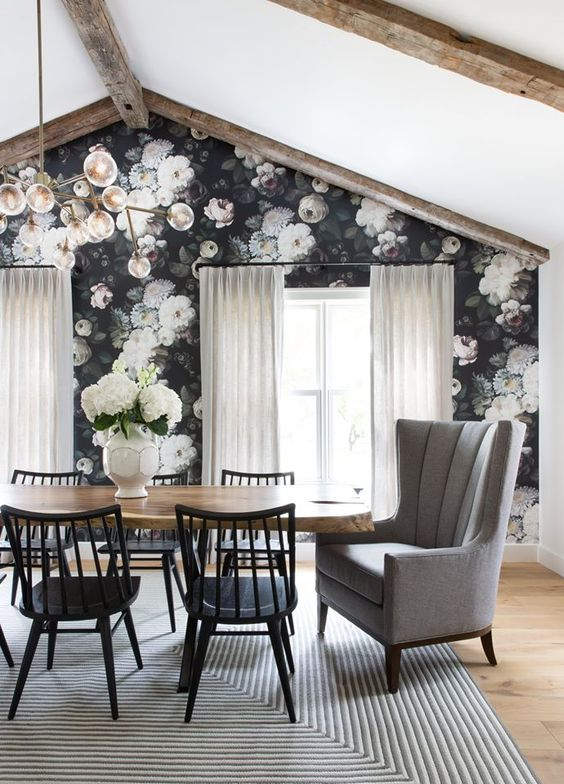 a stylish dining room with a moody floral wall, a live edge table, black chairs, wooden beams and a grey chair