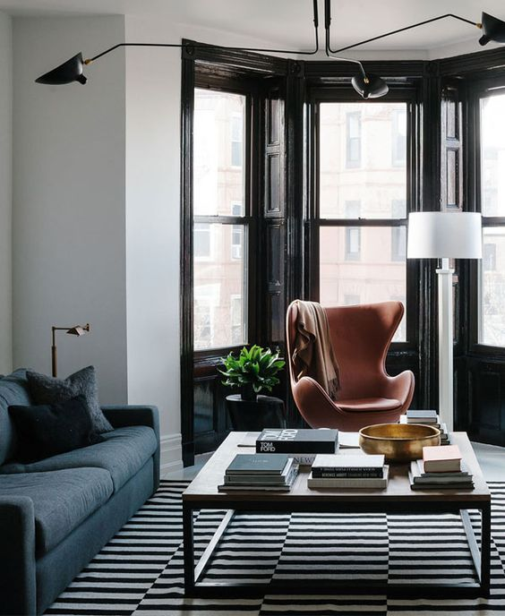 a stylish living room with a black framed bay window finished with a leather chair, potted plants and a lamp looks gorgeous