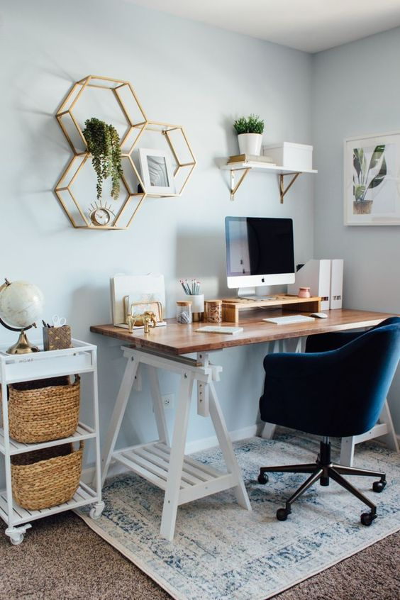a stylish modern home office with a trestle desk, a navy chair, a cart with baskets, hex shelves with potted greenery